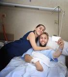 Pares jovenes que toman la foto del selfie en el sitio de hospital con el hombre que miente en cama de la clínica Fotografía de archivo libre de regalías