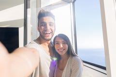 Pares jovenes que toman la mujer de la foto de Selfie y al hombre asiáticos de abarcamiento de los hispanos sonrisa feliz Foto de archivo libre de regalías
