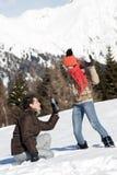 Pares jovenes que toman las fotos en la nieve Imagen de archivo libre de regalías