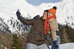 Pares jovenes que toman las fotos en la nieve Imágenes de archivo libres de regalías
