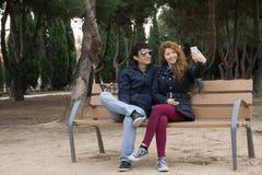 Pares jovenes que toman selfies en el parque en un winter& x27; día de s Fotografía de archivo