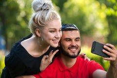 Pares jovenes que toman un selfie con el teléfono elegante Foto de archivo libre de regalías