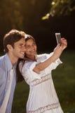 Pares jovenes que toman un selfie en el parque Fotografía de archivo libre de regalías