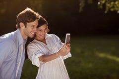 Pares jovenes que toman un selfie en el parque Fotos de archivo libres de regalías