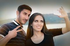Pares jovenes que toman un Selfie junto Imagen de archivo libre de regalías