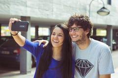 Pares jovenes que toman una fotografía del autorretrato del selfie de ellos mismos Imagen de archivo libre de regalías