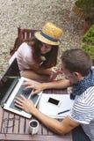 Pares jovenes que trabajan con el ordenador portátil adentro al aire libre Imagenes de archivo