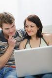 Pares jovenes que trabajan en la computadora portátil Imágenes de archivo libres de regalías