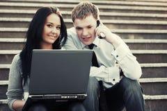 Pares jovenes que trabajan en la computadora portátil Foto de archivo