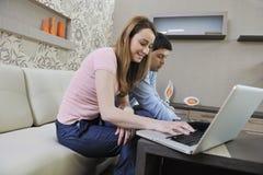 Pares jovenes que trabajan en la computadora portátil en el país Foto de archivo libre de regalías