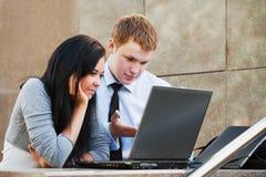 Pares jovenes que trabajan en la computadora portátil Fotos de archivo