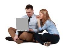 Pares jovenes que trabajan en una computadora portátil foto de archivo