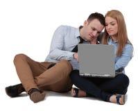 Pares jovenes que trabajan en una computadora portátil Fotografía de archivo libre de regalías