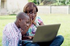 Pares jovenes que trabajan en una computadora portátil Imagen de archivo libre de regalías