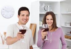 Pares jovenes que tuestan con los vidrios de vino rojo Fotografía de archivo