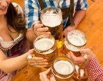 Pares jovenes que tuestan en tienda de la cerveza de Oktoberfest imagenes de archivo