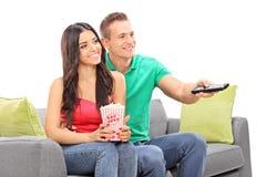 Pares jovenes que ven la TV asentada en un sofá Foto de archivo libre de regalías