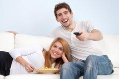 Pares jovenes que ven la TV en casa Foto de archivo libre de regalías