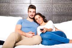Pares jovenes que ven la TV junto en el sofá Imagen de archivo