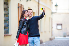 Pares jovenes que viajan el días de fiesta en la sonrisa de Europa feliz Familia caucásica que hace el selfie en calles viejas va Imagen de archivo