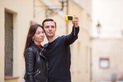Pares jovenes que viajan el días de fiesta en la sonrisa de Europa feliz Familia caucásica que hace el selfie en calles viejas va Imagen de archivo libre de regalías