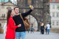Pares jovenes que viajan el días de fiesta en la sonrisa de Europa feliz Familia caucásica que hace selfie en Karlov popular la m Imagen de archivo