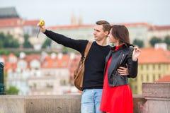 Pares jovenes que viajan el días de fiesta en la sonrisa de Europa feliz Familia caucásica que hace selfie en Karlov popular la m Imágenes de archivo libres de regalías