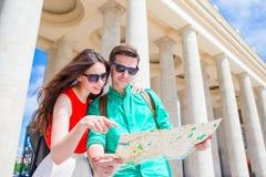 Pares jovenes que viajan el días de fiesta en la sonrisa de Europa feliz Familia caucásica con el mapa de la ciudad en busca de a Foto de archivo libre de regalías