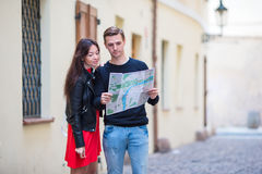 Pares jovenes que viajan en la sonrisa de los días de fiesta al aire libre feliz Familia caucásica con el mapa de la ciudad en bu Fotografía de archivo