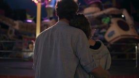 Pares jovenes que visitan una arcada del parque de atracciones junto y que abrazan mientras que se coloca al lado de un paseo del almacen de metraje de vídeo