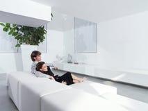 Pares jovenes relajados en casa Imagen de archivo