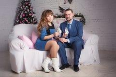 Pares jovenes relajados en casa en sala de estar brillante con los vidrios de champán Imagenes de archivo
