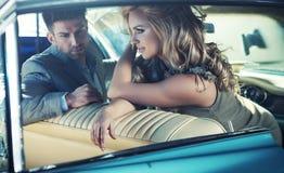 Pares jovenes relajados en el coche retro Imagen de archivo