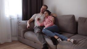 Pares jovenes relajados que mienten en el sofá gris en casa en la sala de estar con el interior del desván y la TV de observación almacen de video