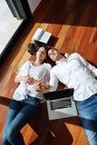 Pares jovenes relajados que trabajan en el ordenador portátil en casa Foto de archivo libre de regalías