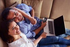 Pares jovenes relajados que trabajan en el ordenador portátil en casa Fotos de archivo libres de regalías