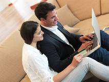 Pares jovenes relajados que trabajan en el ordenador portátil en casa Fotografía de archivo