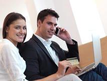 Pares jovenes relajados que trabajan en el ordenador portátil en casa Fotos de archivo
