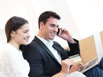 Pares jovenes relajados que trabajan en el ordenador portátil en casa Fotografía de archivo libre de regalías