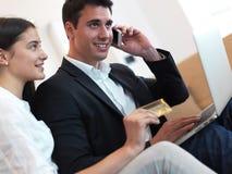 Pares jovenes relajados que trabajan en el ordenador portátil en casa Imagenes de archivo