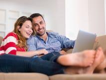 Pares jovenes relajados que trabajan en el ordenador portátil en casa Foto de archivo