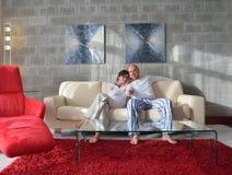 Pares jovenes relajados que ven la TV en casa Fotografía de archivo
