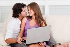 Pares jovenes románticos con la computadora portátil imagenes de archivo