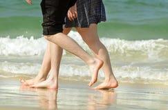 Pares jovenes románticos el día de fiesta que camina a lo largo de la playa Fotos de archivo