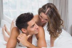 Pares jovenes románticos en cama en casa Imagen de archivo libre de regalías