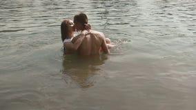 Pares jovenes románticos en el lago que se besa mientras que abraza Hombre joven hermoso que lleva a cabo su girlfdriend bonito e almacen de video