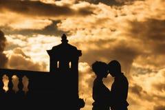 Pares jovenes románticos en la pared de la fortaleza en la puesta del sol fotos de archivo