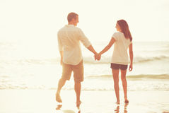 Pares jovenes románticos en la playa en la puesta del sol Imagenes de archivo