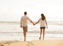 Pares jovenes románticos en la playa en la puesta del sol Imágenes de archivo libres de regalías
