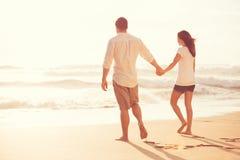 Pares jovenes románticos en la playa en la puesta del sol Fotografía de archivo